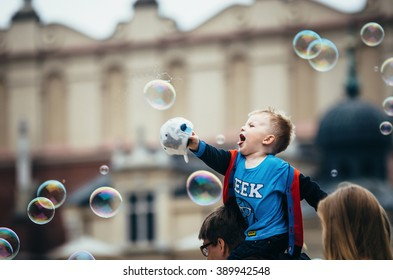 KRAKOW, POLAND - JUNE 27, 2015: Adorable little boy sits on dad's shoulders and touches the giant bubbles at the street.