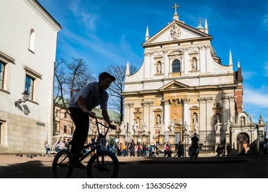Krakow, Poland - March 22, 2019 - a boy on a cycle on a square in front of Saints Peter and Paul Church