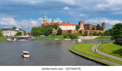 Krakow, Poland - May 20, 2019: Spring view on Wawel Castle, Vistula River, spring park, bicycle lane and walking tourists