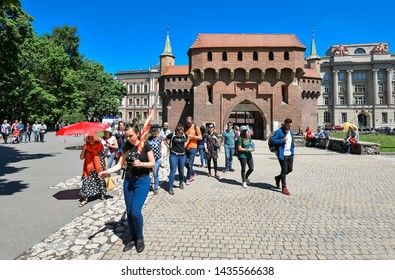 Krakow, Poland - May 20, 2019: The Krakow Barbican - a fortified outpost. It is a historic gateway leading into the Old Town of Krakow, Poland. Group of tourists on excursions near Krakow Barbican