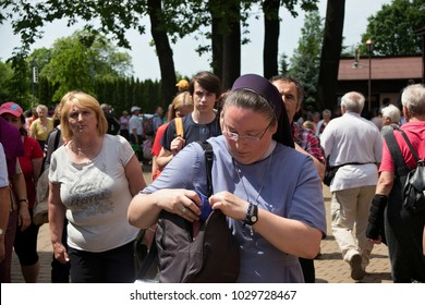 KRAKOW, POLAND - MAY 28, 2016: Tourists and Pilgrims in park near Basilica of the Divine Mercy of Sanctuary in Lagiewniki. Millions of pilgrims from around the world visit sanctuary every year.