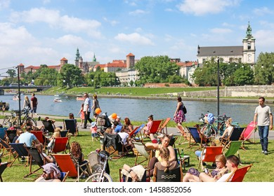 KRAKOW, POLAND - MAY 29, 2016:  Young people relaxing themselves on sunbeds by the river in Krakow, Poland.