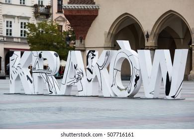 Krakow, Poland - October 27, 2016: Krakow sign in large white capital letters on Rynek Glowny, the old city market square.