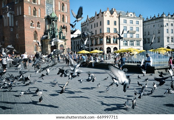 KRAKOW, POLAND - SEPTEMBER 1, 2016. People and pigeons ,tourists attraction in Rynek Glowny ,Main Market Square in the Old city of Krakow, Poland.