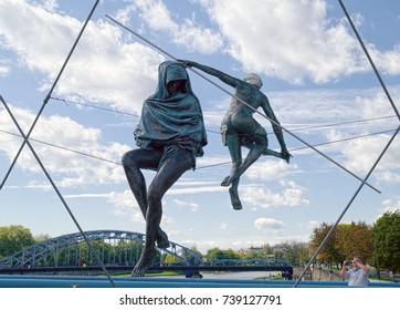 KRAKOW, POLAND - SEPTEMBER 13, 2017: The Balancing Sculptures of Polish artist Jerzy Kedziora, part of sculptural group exposed on Bernatek Footbridge across Vistula river in Krakow.