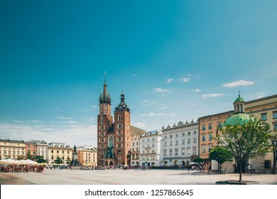 Krakow, Poland. St. Mary's Basilica And Cloth Hall Building. Famous Old Landmark Church Of Our Lady Assumed Into Heaven. Saint Mary's Church In  Of The Main Market Square. UNESCO World Heritage Site.