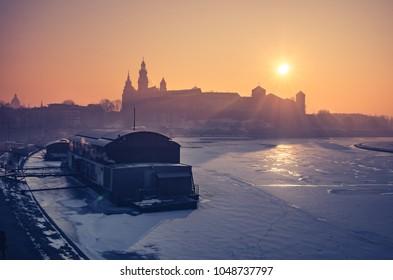 Krakow, Poland, Wawel Castle and Wawel cathedral in the winter over frozen Vistula river, sunrise