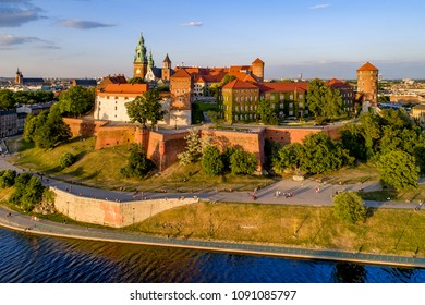 Krakow, Poland. Wawel Hill, royal Cathedral and castle. Aerial view in sunset light. Vistula River and far view of St. Mary (Mariacki) church on the left. Riverbank with promenade and walking people.