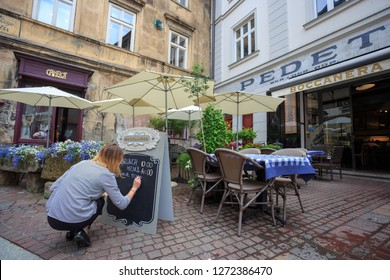 Krakow/Cracow, Poland - Jun 23. 2018: Woman manager is chalking the daily menu on the blackboard in front of a small restaurant Boccanera, on Unfaithful Thomas Lane street, next to Café Camelot.