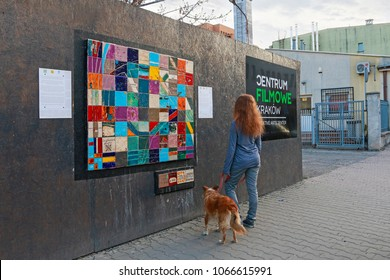 KRAKOW,POLAND - APRIL 11, 2018: Street art, woman looking at mosaic made by the local community of Zablocie district in Krakow, Poland.