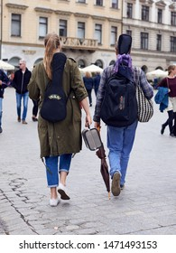 Krakow/Poland - June 13 2018: Two young street musicians, wearing casual clothes and jeans, with guitar and ukulele on their backs are walking away  in Krakow old city.