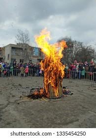 Kramatorsk, Ukraine - 10h March, 2019: People celebraites the Maslenitsa, eastern Slavs holiday. Mass festival with burning down a straw effigy of winter. Vertical image.