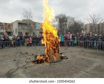 Kramatorsk, Ukraine - 10h March, 2019: People celebraites the Maslenitsa, eastern Slavs holiday. Mass festival with burning down a straw effigy of winter.