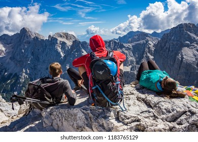 KRANJSKA GORA, SLOVENIA - SEPTEMBER 9th 2018: Three mountaineers sitting on the rock on the top of the Prisojnik mountain in Julian Alps enjoying the view on a autumn afternoon