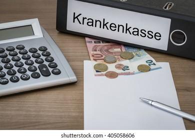 Krankenkasse (German Health Insurance) written on a binder on a desk with euro money calculator blank sheet and pen