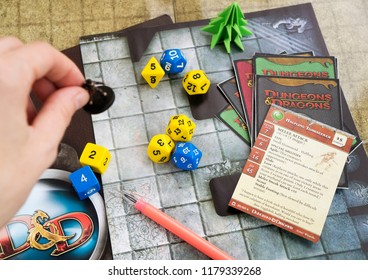 Krasnodar, Russia, 14 September 2018: Playing Dungeons and Dragons fantasy role play game. Dices, cards; hand holding a miniature figure of rpg character. Board games.