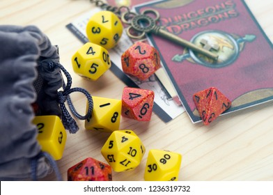 Krasnodar, Russia, 21 November 2018: Playing Dungeons and Dragons, a role play game. Dices, grey bag and cards lying on wooden surface. Decorative beautiful key.