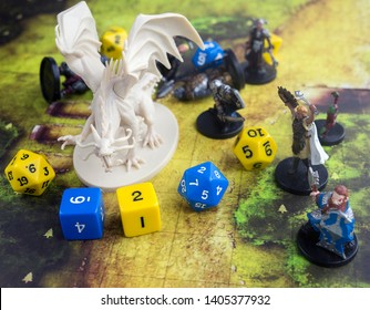 Krasnodar, Russia, 23 May 2019: Playing dungeons and dragons game. Map with a figure of dragon and plastic figures of rpg characters, dices scattered.