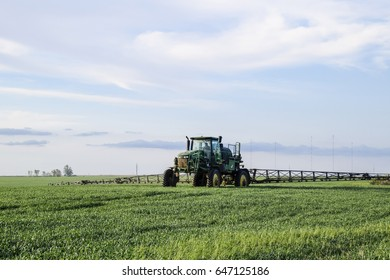 Krasnodar, Russia - April 27, 2017: Tractor with high wheels is making fertilizer on young wheat. The use of finely dispersed spray chemicals. Tractor with spray device for finely dispersed fertilizer