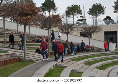 KRASNODAR, RUSSIA - DEC. 03, 2017: Townspeople rest in the amphitheater of the new modern multi-level southern city park in the winter evening of the weekend