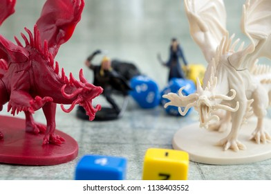 Krasnodar, Russia, July 19, 2018: Playing Dungeons and Dragons. Miniature fugures of rpg characters,  dices and two dragons standing opposite. Board games.