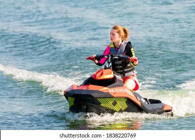 Krasnodar, Russia - July 25, 2020: Jet ski watercraft beautiful Caucasian woman driver driving water bike on summer sunny day