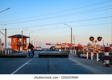 Krasnodar, Russia - March 31, 2018: Railroad crossing with a barrier and a traffic light.