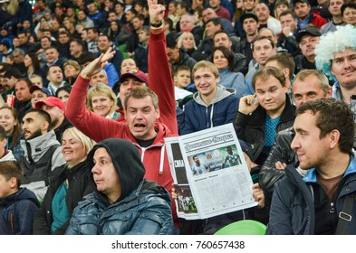 KRASNODAR, RUSSIA - November 14, 2017: A fan with a newspaper in his hands, and next to an emotional fan who screams during a friendly match, 2017, Russia