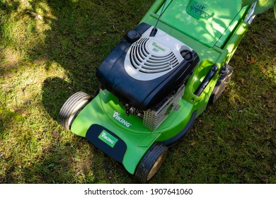 Krasnodar, Russia - November 8, 2020: Viking lawn mower stands on lawn against backdrop of greenery of landscaped garden. Lawnmower body made of green plastic. Gasoline engine under plastic cover.