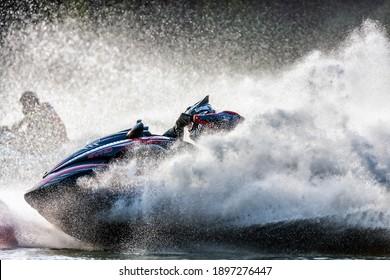 Krasnodar, Russia - October 25, 2020: Jet ski racers drive watercrafts splashing in sunset while racing at South Russian Aquabike Championship