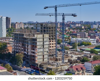 Krasnodar, Russia - October 6, 2018: Construction of a new residential building on monolithic frame technology in the area with the existing infrastructure. Two tower cranes are working.