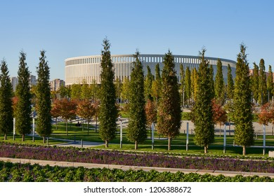 Krasnodar, Russia - October 7, 2018: Slender rows of evergreen and deciduous trees on the promenade in the park of Krasnodar or Galitsky in the autumn sunny day. In the background is the building