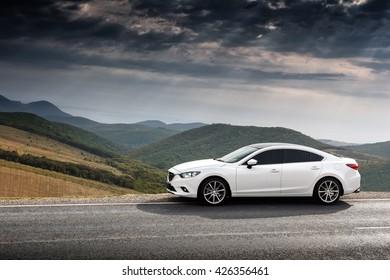 Krasnodar, Russia - September 07, 2014: White Car Mazda 6 parket at countryside asphalt road near green mountains at daytime