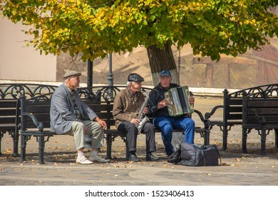Krasnodar, Russia - September 28, 2019: older men sit on a bench in the park and play musical instruments in autumn sunny day