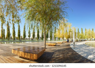 Krasnodar, Russia-October 19, 2018: wooden benches under the willows on the terrace near the pond of the new city Park Krasnodar near the stadium of the football club - a great place to relax