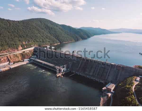 Krasnoyarsk hydroelectric station dam, hydro power plant on Enisey river from aerial view. Krasnoyarsk reservoir. Industrial landscape