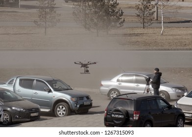 KRASNOYARSK, Krasnoyarsk Region/ RF- April 5, 2015: Unmanned aerial vehicle - quad copter with a camera and video broadcast is controlled by a man in a car parking in the Krasnoyarsk city.