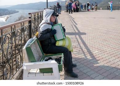 Krasnoyarsk, Krasnoyarsk Region / RF - April 6, 2019: A man earns money playing the accordion for tourists, sitting on a bench on the observation deck over the Yenisei.