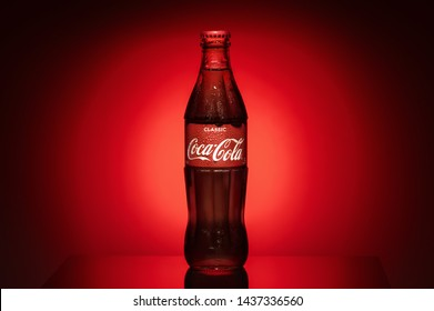 Krasnoyarsk, Russia, 29 June 2019: Coca-Cola Classic in a glass bottle on dark toned foggy reds -black Background. Coke is the most popular carbonated soft drink. Horizontal maket.