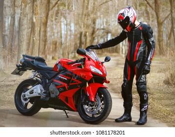 KRASNOYARSK, RUSSIA - April 21, 2018: Beautiful motorcyclist in full gear and helmet on a red and black Honda 2005 CBR 600 RR (PC37)