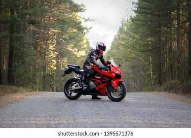 KRASNOYARSK, RUSSIA - April 23, 2019: Beautiful motorcyclist in full gear and helmet on a red and black Honda 2005 CBR 600 RR (PC37).