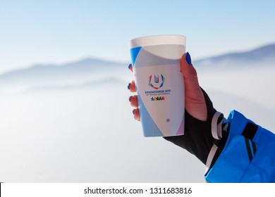 Krasnoyarsk, Russia, February 2019: cups in hand with a brand under the 2019 Universiade. Symbol of the 2019 Universiade