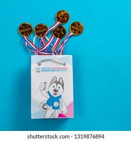"Krasnoyarsk, Russia, February, 2019: the symbol of the ""Universiade 2019"" in Krasnoyarsk, ""U-Laika"" and medals in a paper bag on a blue background"