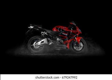 KRASNOYARSK, RUSSIA - JULY 12, 2017: Red and black sportbike Honda CBR 600 RR 2005 PC37. Isolated on black background with smoke. Studio photography