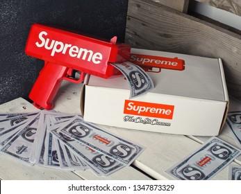 Krasnoyarsk, Russia - July 5, 2017: Red Supreme Money Launch Gun Cash Cannon with 1000 Dollar Bills Notes shot on wooden background.