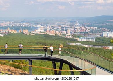 Krasnoyarsk, Russia - June 17, 2021: People sightseeing and are photographed on the observation deck on Nikolaevskaya Sopka. Cityscape view of Krasnoyarsk