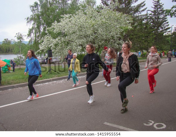 Krasnoyarsk, Russia, - June 2, 2019: Girls are engaged in fitness in outdoors. Green grass and trees. The concept of sports in the city.