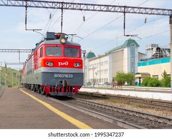 Krasnoyarsk, Russia - June 20, 2021: red commuter passenger train with logo Russian Railways at the railway station.