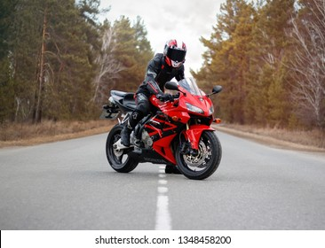 KRASNOYARSK, RUSSIA - March 24, 2019: Beautiful motorcyclist in full gear and helmet on a red and black Honda 2005 CBR 600 RR (PC37).