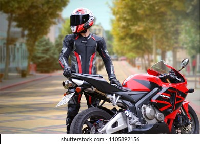 KRASNOYARSK, RUSSIA - May 29, 2018: Beautiful motorcyclist in full gear and helmet on a red and black Honda 2005 CBR 600 RR (PC37)